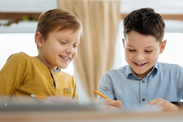 Spaß haben. fröhliche angenehme jugendliche jungen, die am tisch sitzen und zusammen zeichnen, während sie lächeln und das bild diskutieren