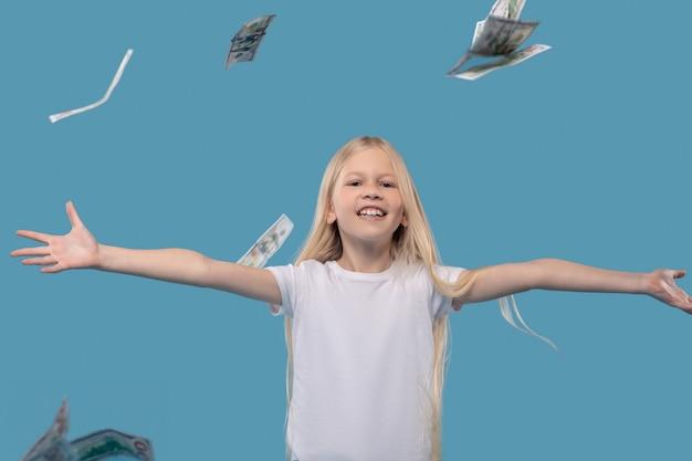 Spaß haben. fröhliches grundschulmädchen im weißen t-shirt, das im studiofoto banknoten hochwirft