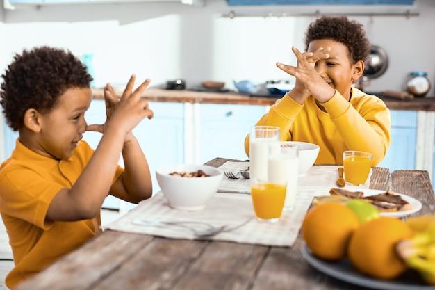Spaß haben. optimistische kleine jungen, die am tisch sitzen, sich gegenseitig die nase zudrücken und beim frühstück lachen