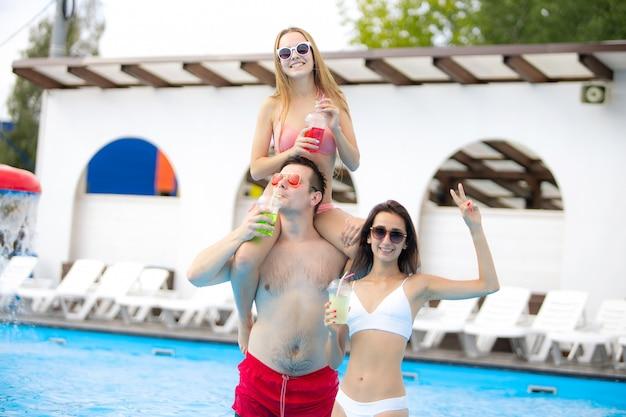 Spaß haben und cocktails mit besten freunden genießen. schöne mädchen und kerl verbringen ihre sommerferien und ferien.