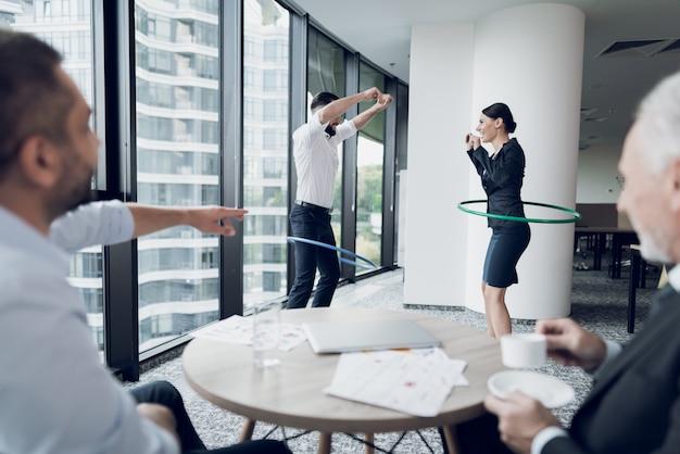 Spaß im büro. ein mann und eine frau drehen hula hoops.