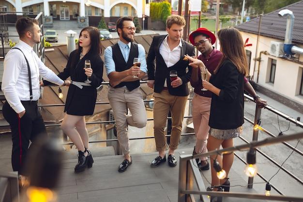 Spaß. junge leute feiern, sehen glücklich aus, feiern im büro oder in der bar. männer und frauen trinken alkohol, reden, lachen. feiertage, wochenende, wirtschaft und finanzen, freundschaftskonzept. teambildung.