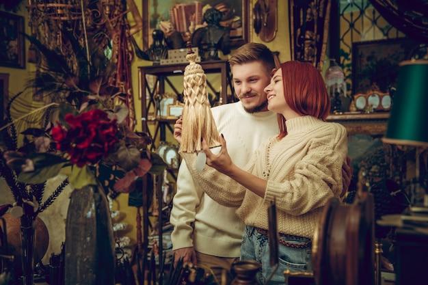 Spaß. lächelnde familie, kaukasisches paar, das nach hauptdekoration und feiertagsgeschenken im haushaltsgeschäft sucht. stilvolle und retro-dinge für grüße oder design. innenrenovierung, zeit feiern.