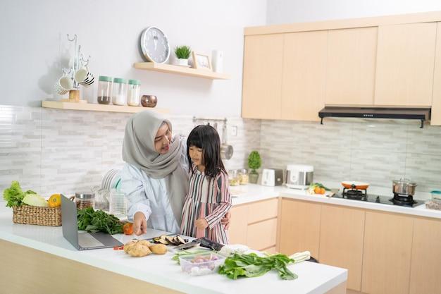 Spaß mit muslimischer frau mit hijab und kind, die gemeinsam das abendessen zubereiten