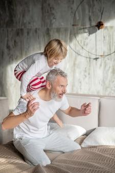Spaß mit papa. glückliches kind, das auf rücken des grauhaarigen freudigen vaters klettert, der auf bett kniet