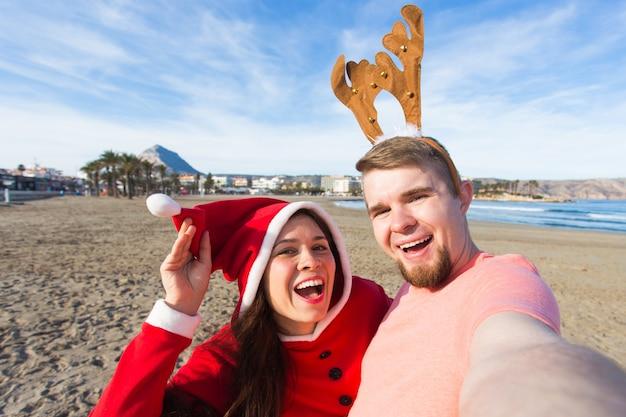 Spaß- und winterferienkonzept - glückliches paar in den weihnachtskostümen, die selfie über sandstrand nehmen
