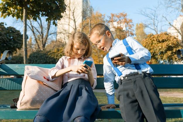 Spaßkinderjunge und -mädchen untersuchen smartphones