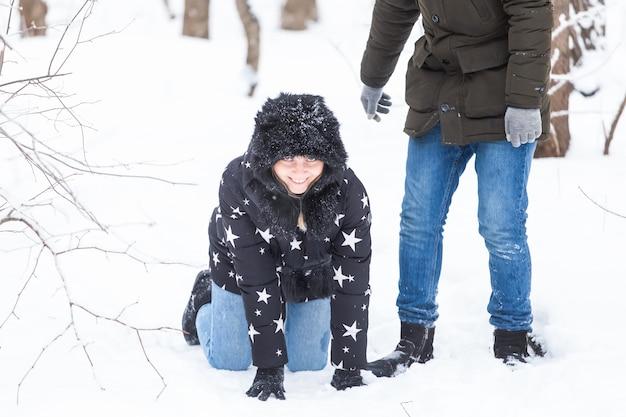Spaßsaison und freizeitkonzept liebespaar spielt winterholz auf schnee