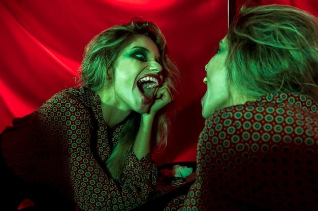Spaßvogelfrau, die im spiegel lacht