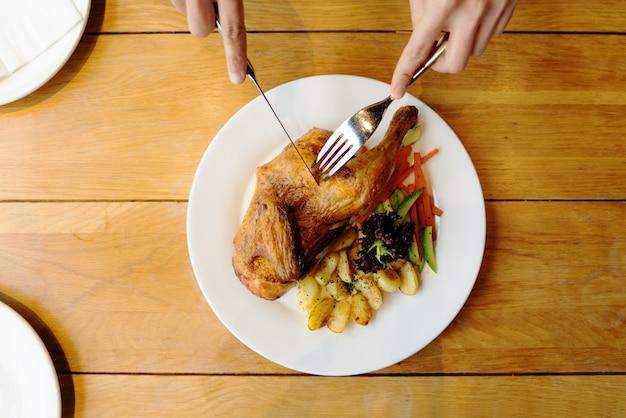 Spatchcocked grillhuhn mit gemüsedraufsicht über weiße platte