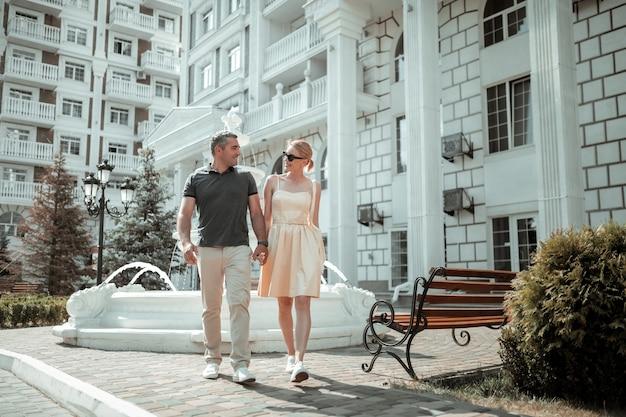 Spazieren sie mit einem geliebten menschen. glücklicher ehemann und ehefrau, die am sonnigen sommertag händchen haltend spazieren gehen.