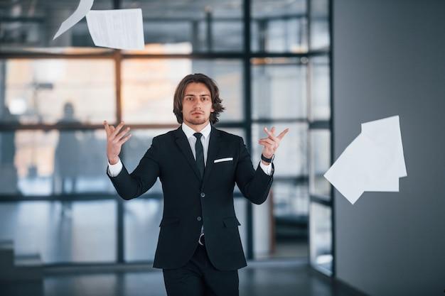 Spaziergänge im büro und dokumente in die luft werfen. porträt des hübschen jungen geschäftsmannes im schwarzen anzug und in der krawatte.