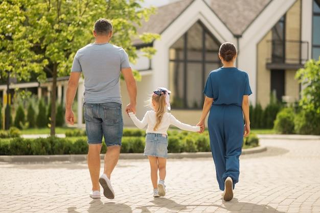 Spaziergang mit tochter. ein paar geschäftsleute, die am wochenende mit ihrem kleinen mädchen in der stadt spazieren gehen