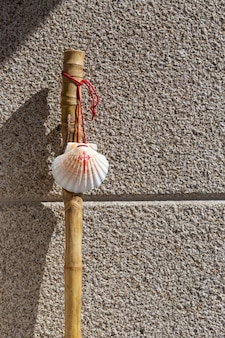Spazierstock und muschel des jakobswegs auf granitsteinmauer. pilgerkonzept von santiago de compostela