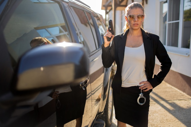 Special federal intelligence agent frau in schwarzem anzug und großem auto