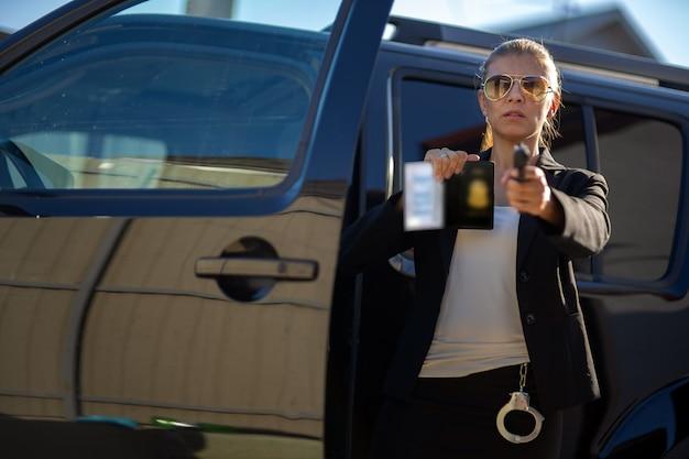 Special federal intelligence agent frau in schwarzem anzug und großem polizeiauto
