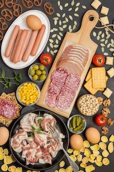 Speck in der pfanne, salamischinken auf schneidebrett, würstchen in weißer platte, gemüse, kekse. zutaten für das englische frühstück