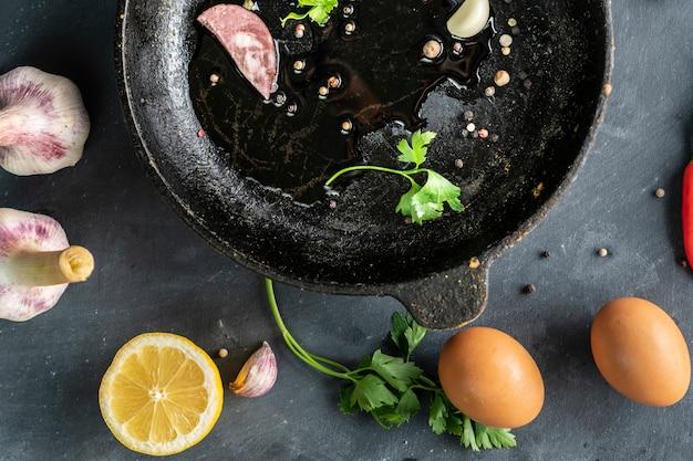 Speck oder geschnittenes fleisch und kräuterblätter auf einer heißen, geölten pfanne, rührei kochen