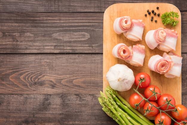 Speck rollt mit tomate, knoblauch, spargel auf hölzernem hintergrund