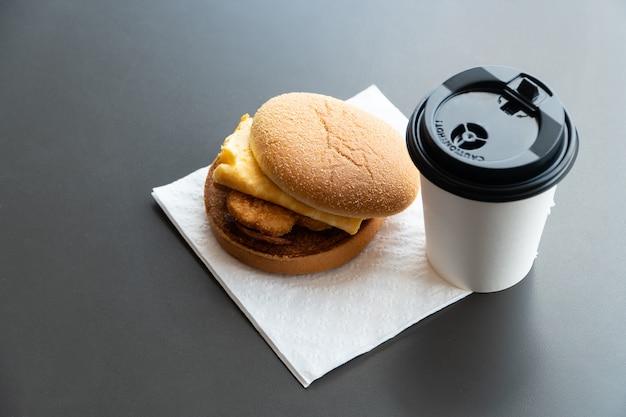 Speck- und omelett-hamburger auf dem papier mit weißbuchkaffeetasse auf dem tisch im schnellrestaurant