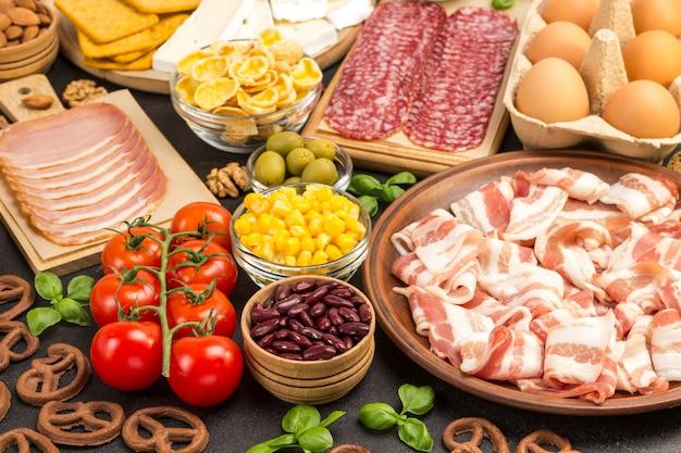 Speck, würstchen, käse, gemüse, kekse, müslieier: zutaten für das kontinentale frühstück.