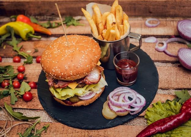 Speckburger mit rindfleisch und pommes frites auf holztisch