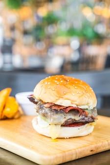 Speckkäseburger mit rindfleisch auf hölzernem brett im restaurant