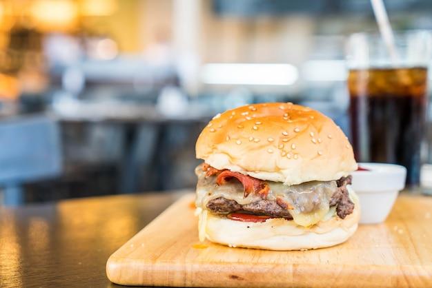 Speckkäseburger mit rindfleisch auf hölzernem brett in der gaststätte