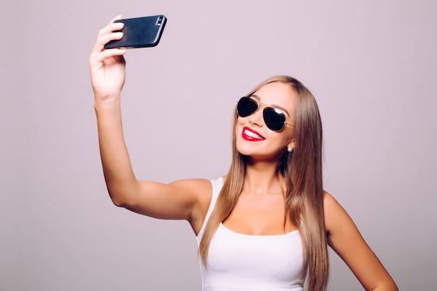 Speichern der erinnerung an ihren neuen stil. porträt der schönen jungen frau in der brille, die ihren hut anpasst, während selfie macht und gegen graue wand steht