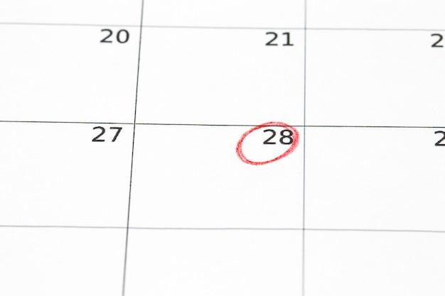 Speichern sie das auf dem kalender geschriebene datum - 28, eingekreist in roter markierung.