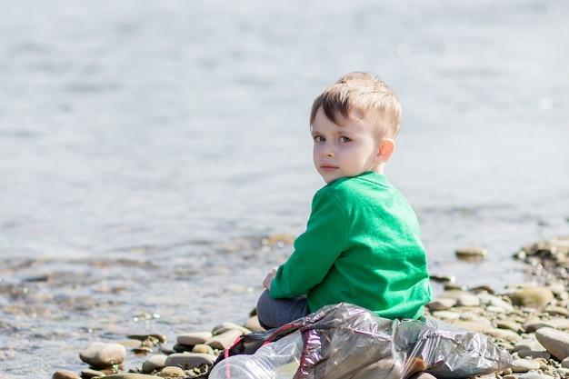 Speichern sie umweltkonzept, ein kleiner junge, der müll und plastikflaschen am strand sammelt, um in den müll geworfen zu werden.