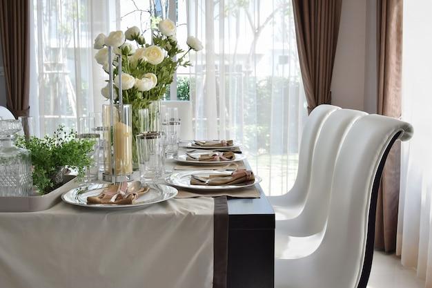Speiseholztisch und bequeme stühle im modernen haus mit elegantem gedeck