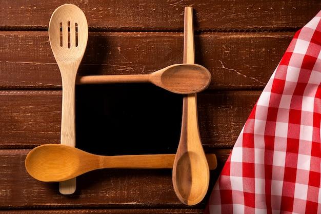 Speisekarte. draufsicht des tafelmenüs, das auf dem rustikalen hölzernen schreibtisch mit löffeln und roter serviette liegt. draufsicht.