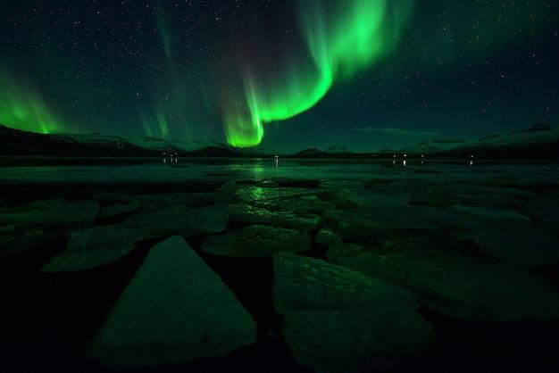 Spektakuläre auroralanzeige bei nacht über mountian, spektakuläre auroralanzeige und stern bei nacht, island