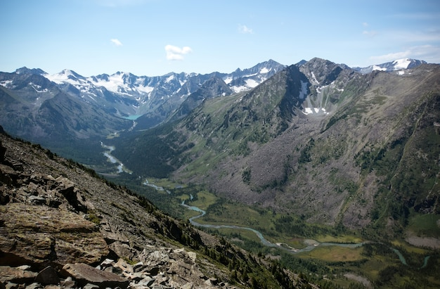 Spektakuläre bergkulisse. fluss mit blauem wasser fließt in einem tal zwischen zwei bergen.