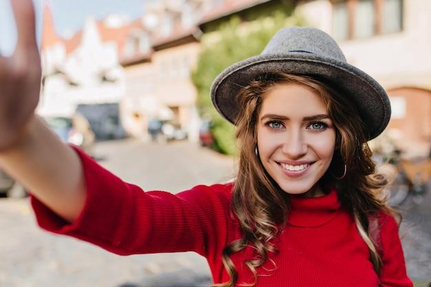 Spektakuläre blauäugige weiße frau im eleganten hut, der selfie mit seligem lächeln macht