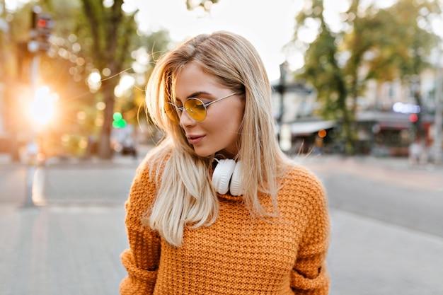 Spektakuläre blonde frau im gestrickten pullover, der am frühen abend im park aufwirft
