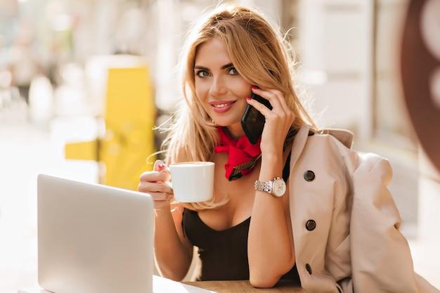 Spektakuläre dame mit glücklichem lächeln, das im café arbeitet und kaffee trinkt
