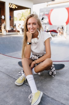 Spektakuläre frau in der schwarzen armbanduhr verträumt auf der straße. schöne skaterfrau, die auf skateboard mit aufrichtigem lächeln sitzt.