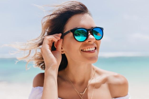 Spektakuläre frau in der trendigen funkelnden sonnenbrille, die guten tag im ocean resort genießt. außenporträt der gegerbten frau, die an der seeküste im sommermorgen aufwirft.