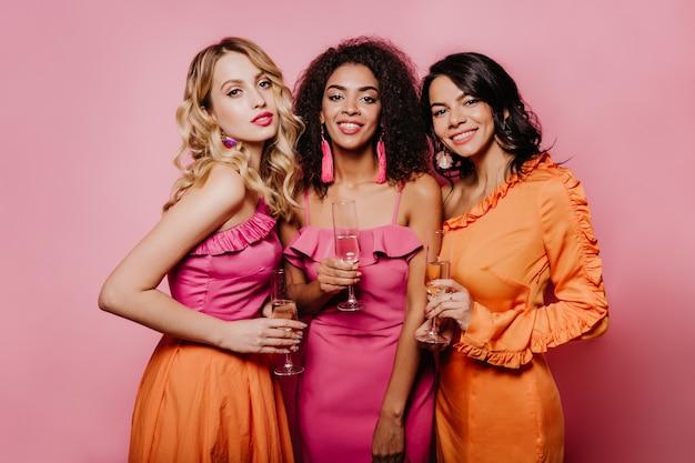 Spektakuläre frauen, die champagner auf rosa wand trinken