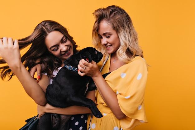 Spektakuläre junge frau, die ihren hund mit liebe betrachtet. wunderbare mädchen spielen mit niedlichen schwarzen welpen und lachen auf gelb.