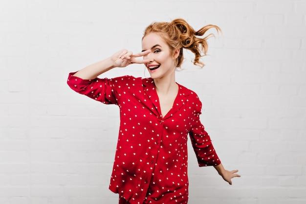 Spektakuläre junge frau, die in niedlicher roter nachtwäsche herumalbert. innenporträt des charmanten mädchens mit pferdeschwanz, der im pyjama tanzt und lächelt.