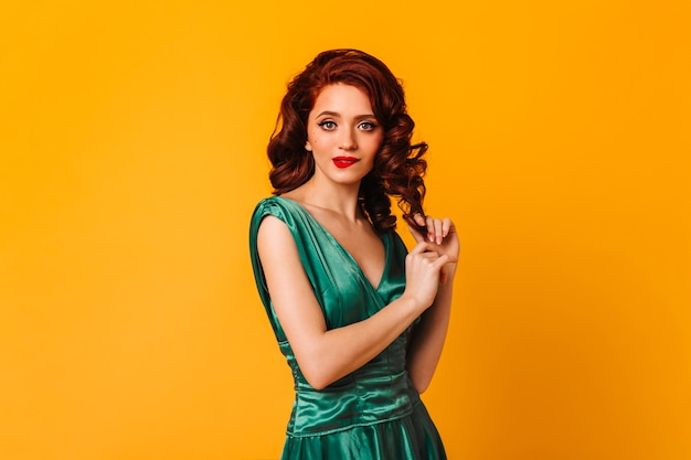 Spektakuläre junge frau, die lockiges ingwerhaar auf gelbem raum berührt. studioaufnahme des erstaunlichen weiblichen modells im grünen kleid.
