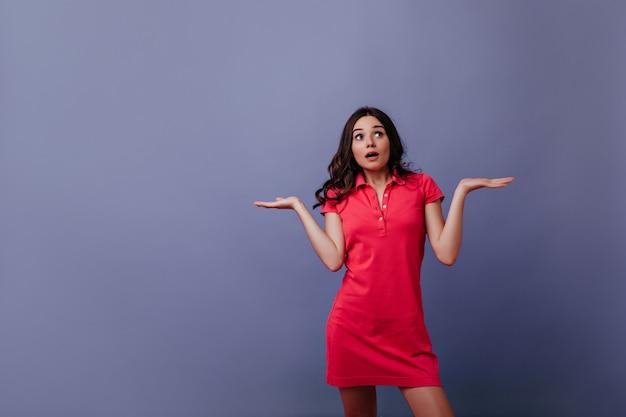 Spektakuläre junge frau im roten outfit, das mit den händen oben aufwirft. überraschtes braunhaariges mädchen, das auf lila wand mit offenem mund steht.