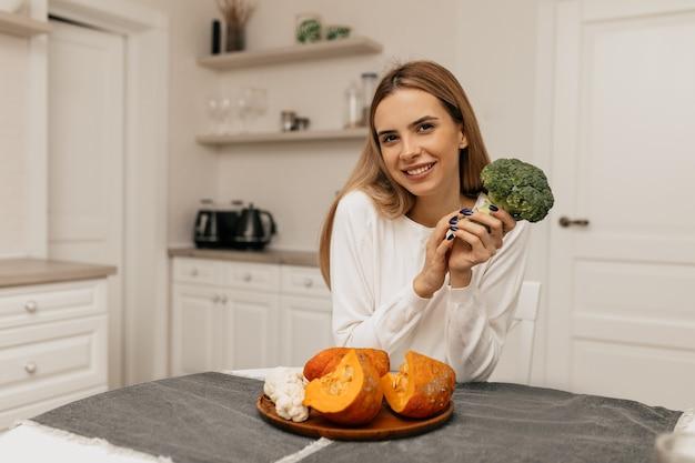 Spektakuläre lächelnde dame, die in der küche mit brokkoli und kürbis sitzt, die für das kochen vorbereiten