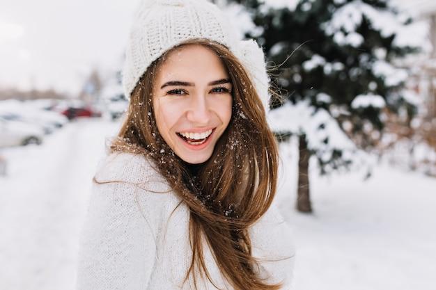 Spektakuläre langhaarige frau, die lacht, während sie auf schnee aufwirft. nahaufnahmefoto im freien des kaukasischen weiblichen modells mit romantischem lächeln, das im park im wintertag kühlt.