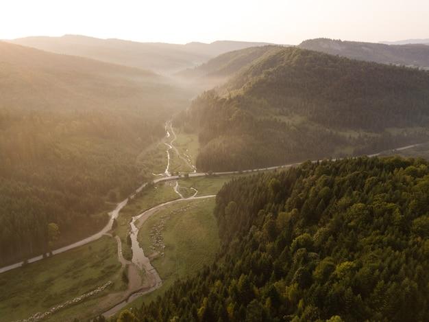 Spektakuläre luftaufnahme zur straße mit bergen, die bei sonnenaufgang von oben aufgenommen wurden, karpatenberge