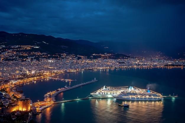 Spektakuläre nacht an der seeküste mit lichtern der stadt und des kreuzfahrtschiffs, die sich im wasser spiegeln