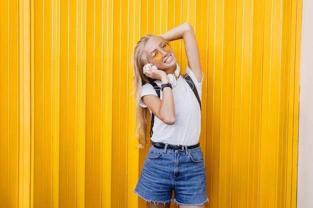 Spektakuläre schlanke frau, die weiße kopfhörer hält. außenporträt des blonden sorglosen mädchens, das auf gelbem hintergrund aufwirft.